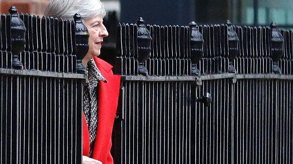 Theresa May in rotem Mantel zwischen schwarzem Zaun