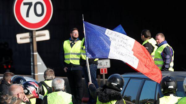 Eine geschwenkte Frankreich-Flagge, Menschen in gelben Warnwesten