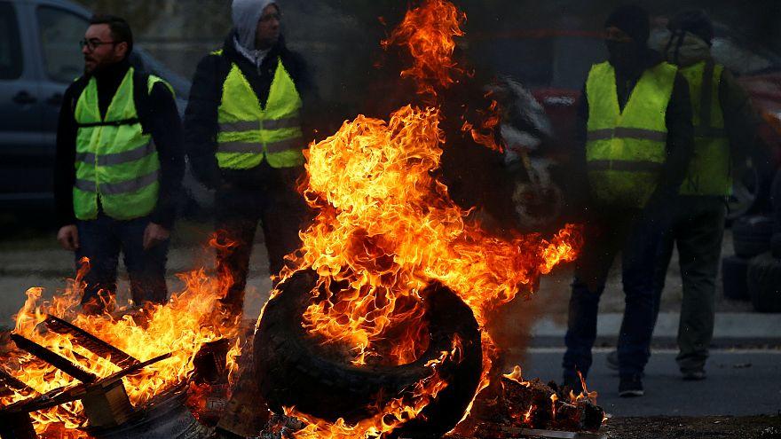 Reifen brennen, im Hintergrund Männer in gelben Warnwesten