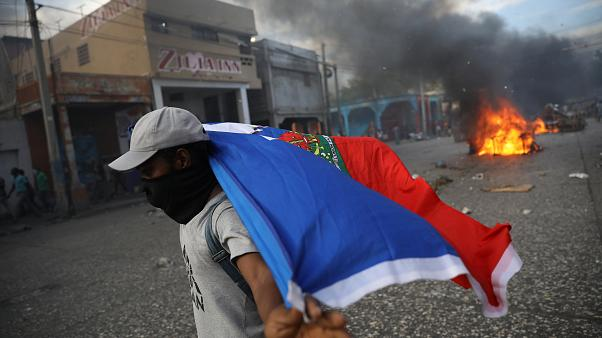 Ein vermummter Mann trägt eine Haiti-Flagge, Im Hintergrund brennen Reifen