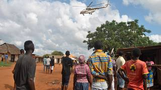 Residents look at a police helicopter patrolling the area