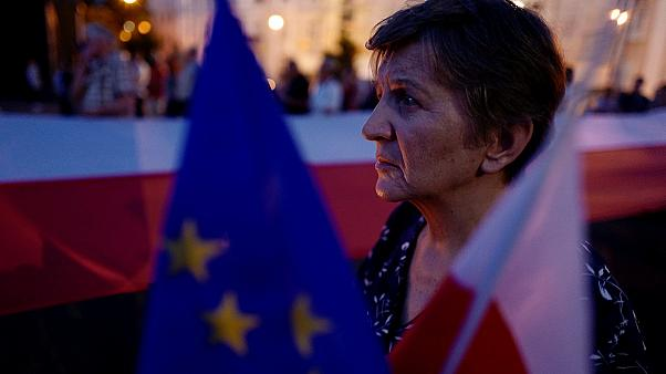 Woman holds flags during an anti-government protest in Warsaw