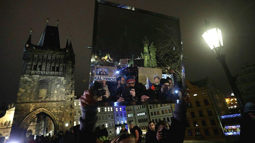 Un manifestante sostiene un espejo durante la manifestación en Praga.