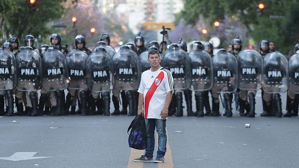 Adepto do River Plate diante de um cordão da polícia argentina
