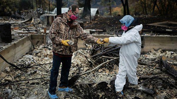 Brett e Vanthy Bizzle recuperam pertences no que resta da casa ardida