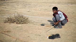 الفلسطيني حمزة أبو شلهوب يحاول اصطياد طيور مغردة في أطلال مطار غزة الدولي