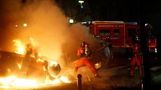 Firemen extinguish burning cars set alight by protesters