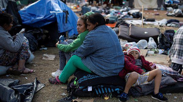 Migrantes esperan a ser trasladados a un nuevo refugio en Tijuana.
