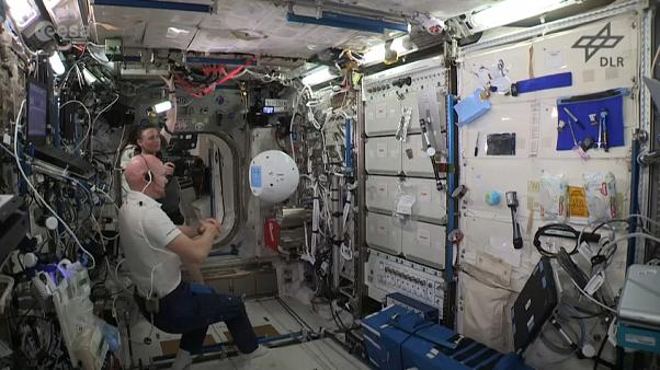 Astronaut interacts with robot aboard ISS