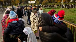 People queue to request asylum outside a Spanish police station on Nov 22