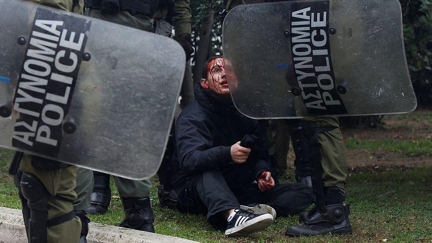 Ein verletzter Demonstrant wird von griechischen Polizisten festgehalten.