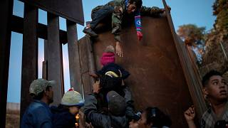 Migrants jump a border fence to cross illegally from Mexico to the U.S.