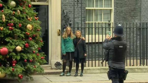 Two women get lots of photos infront of 10 Downing St.