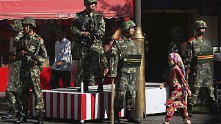 Doğu Türkistan'ın Urumçi kentinde, Çinli askerlerin önünden geçen Uygur kız
