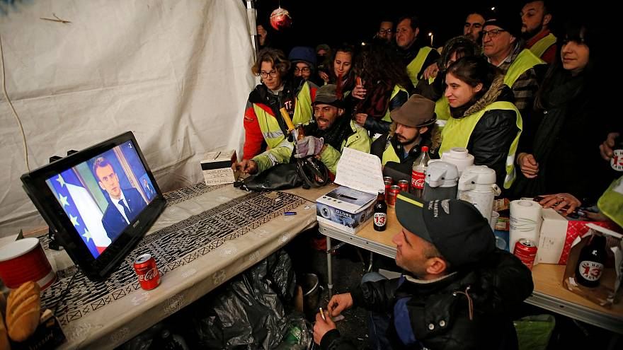 Protesters watch French President Emmanuel Macron on a TV screen on Dec 10