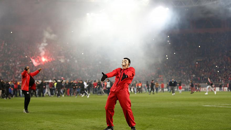 An Olympiacos FC fan celebrating the club's win against Milan