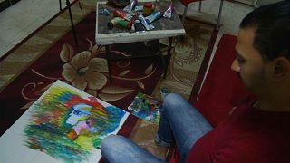 تعرف على رضا فضل.. فنان يرسم بفمه وقدميه