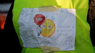 """A protester wears a yellow vest bearing the slogan """"don't give up."""""""