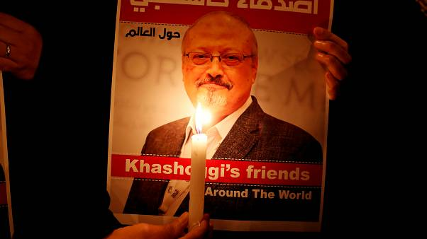 A demonstrator holds a poster with a picture of Saudi journalist Jamal Khas