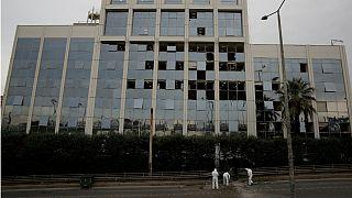 Investigadores forenses recolhem vestígios diante do edifício da Skai TV
