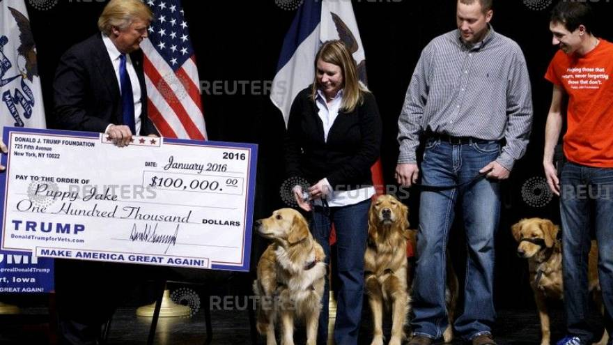 Donald Trump presents a mock check from the Trump Foundation