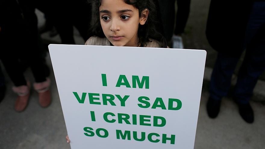A girl in Morocco holds sign in front of Denmark's embassy in Rabat