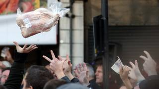 Shoppers bid for cuts of meat during a Christmas Eve auction in London