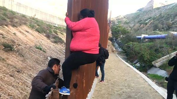 شاهد: مهاجرون يتسلقون السياج الحدودي في المكسيك للعبور إلى الولايات المتحدة