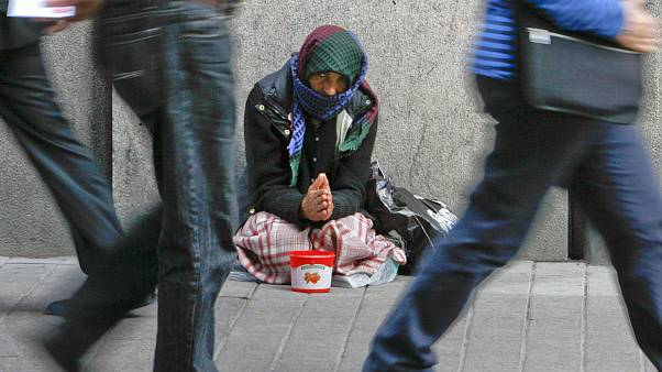 A woman begs for money on a street in downtown Helsinki.