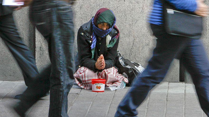 A woman begs for money on a street in downtown Helsinki.