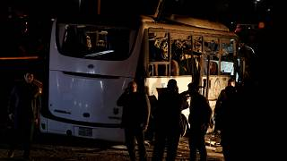 Riot police secure a scene of a bus blast in Giza