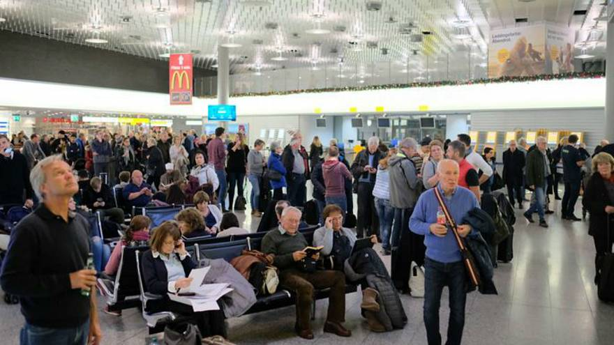 Passengers inside Hanover airport wait as flights are suspended