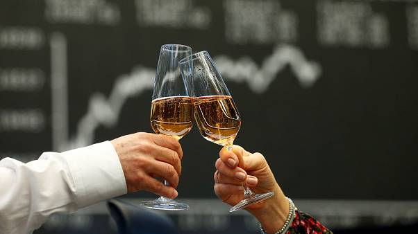 Traders raise their glasses at the stock exchange in Frankfurt