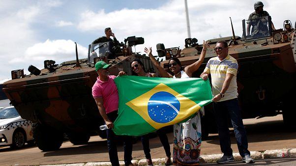 Menschen halten die brasilianische Flagge vor Militärfahrzeugen
