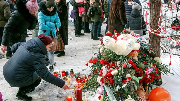 People leave tributes near the site of the partially collapsed building