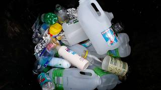 Plastic bottles and containers are seen in a domestic recycling bin