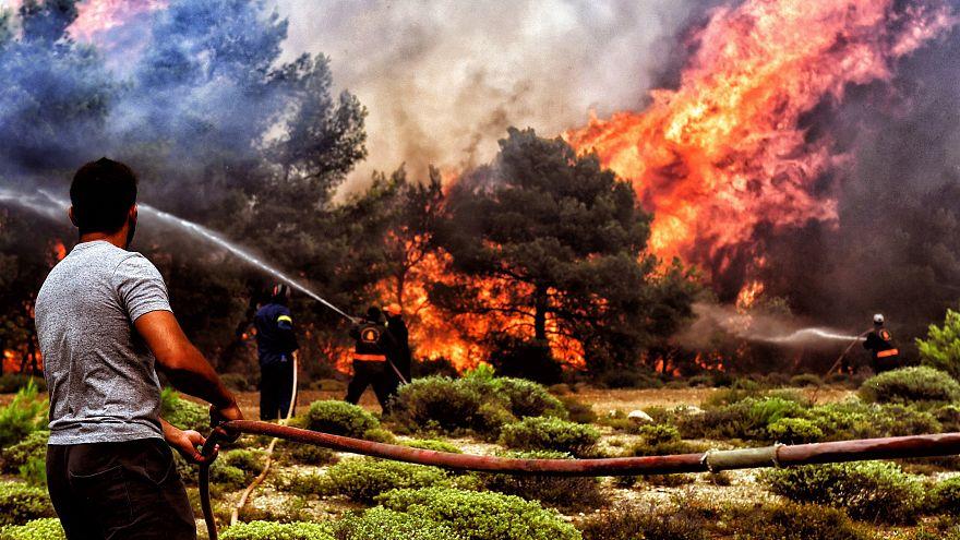 Tűzoltók és önkéntesek küzdenek a tűzzel a görög Lutrakinál július 24-én