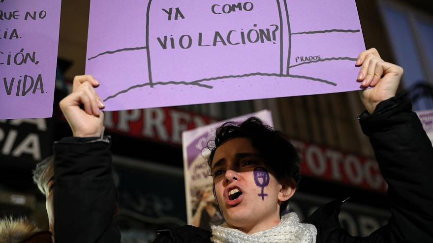 "A woman protests in Madrid with a ""Does it count as rape?"" sign on Dec 5."