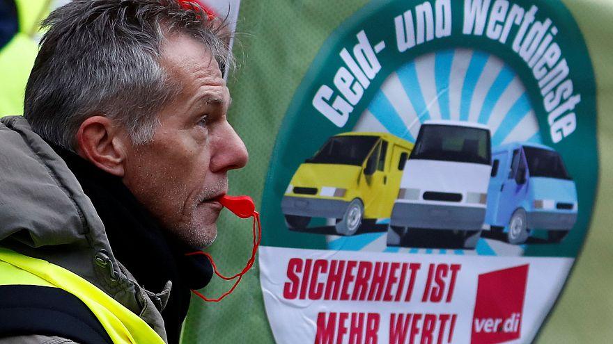 Ein Streikender mit Trillerpfeife vor einem ver.di-Banner
