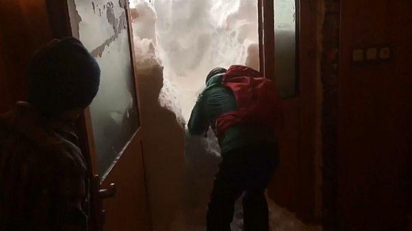 EIn Mann in Skikleidung gräbt sich durch Schnee im Türrahmen