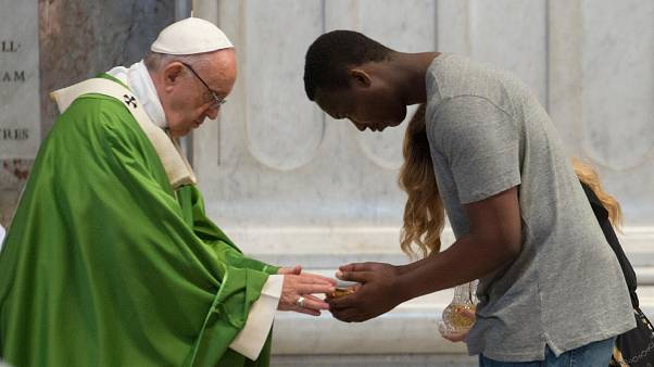 Pope Francis is greeted by a migrant as he celebrates a mass for migrants