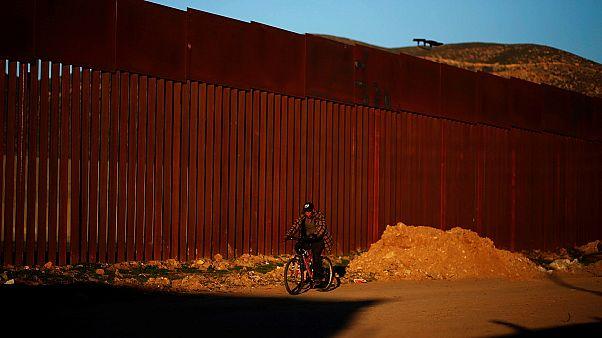 A man cycles along the US border in Tijuana, Mexico.