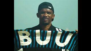 """Samuel Eto'o hält einen schwarz-blauen Schal mit der Aufschrift """"BUU"""""""