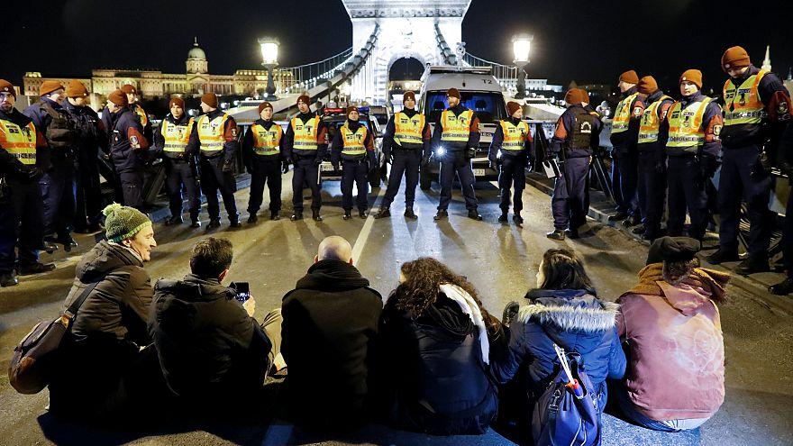 Rendőrök állnak a Lánchídon ülő demonstrálókkal szemben Budapesten