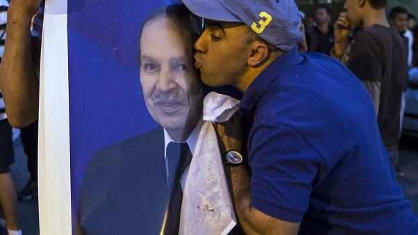 مواطن جزائري مؤيد للرئيس عبد العزيز بوتفليقة يقبل صورته، نيسان/2014
