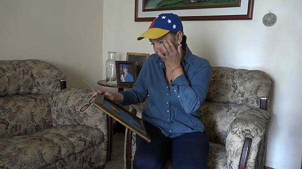 Nelly Pompa cries as she looks at a picture of her son Miguel