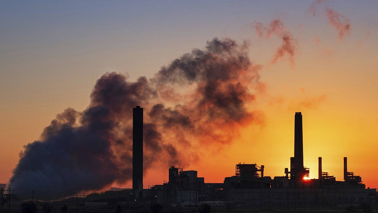 The sun rises behind a coal-fired power plant
