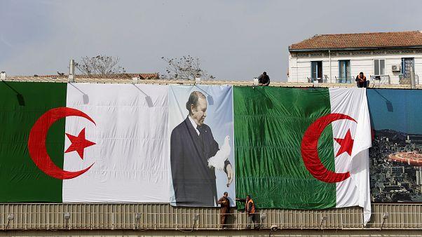 عمال جزائريون يعلقون علم بلادهم قبيل الانتخابات النيابية في 2017