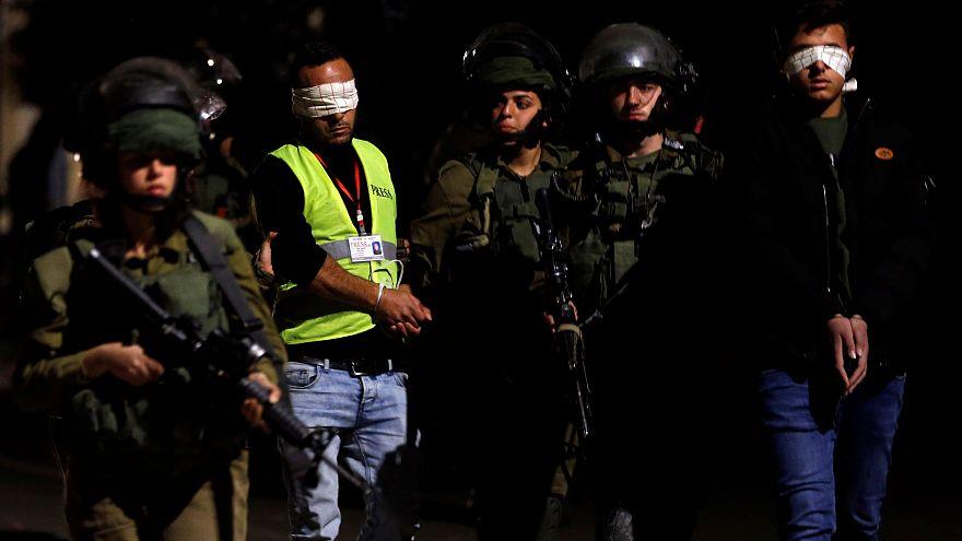 İsrail askerleri Batı Şeria'da bir Filistinli kameramanı göz altına alırken