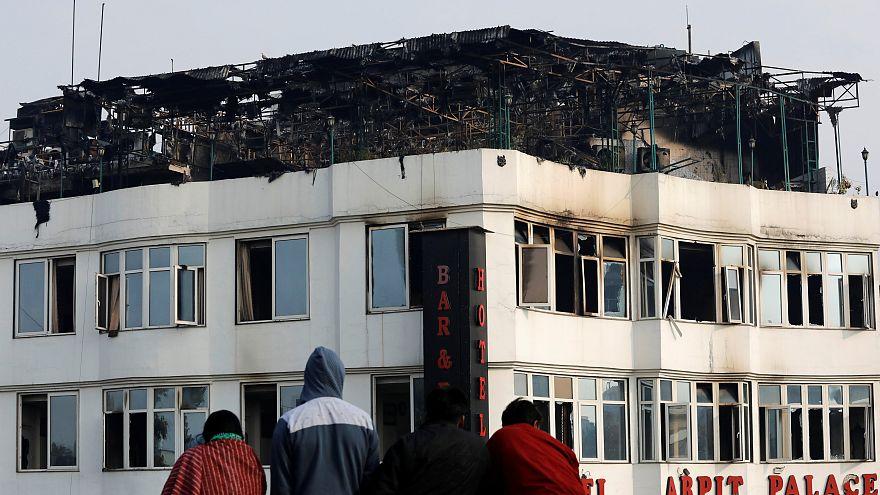 أشخاص على سطح مبنى ينظرون إلى الفندق حيث اندلعت النيران